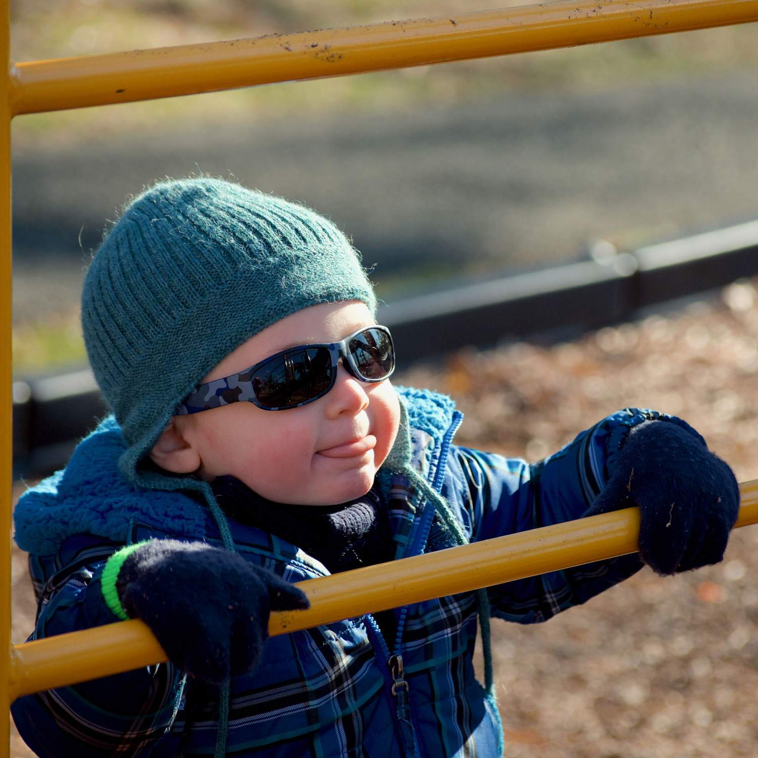 Baby at a playground with sunglasses on