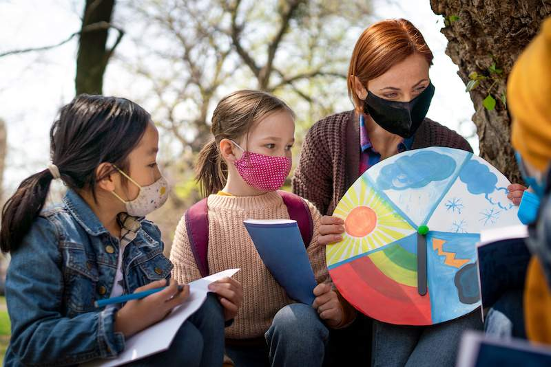 Students in the outdoors with masks on learning from a teacher