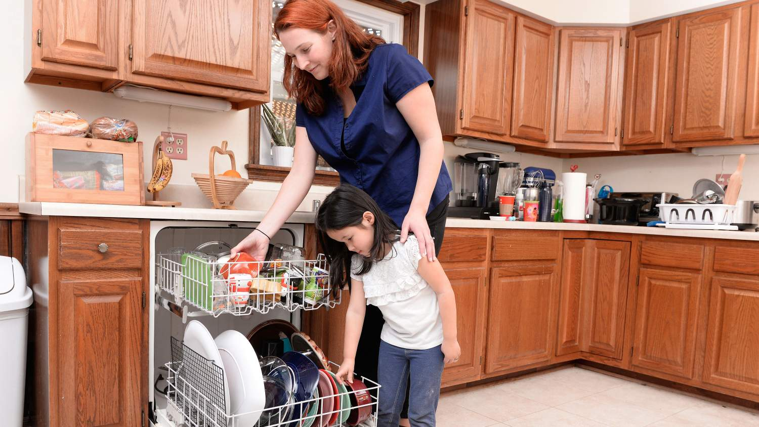 Family loads a dishwasher together