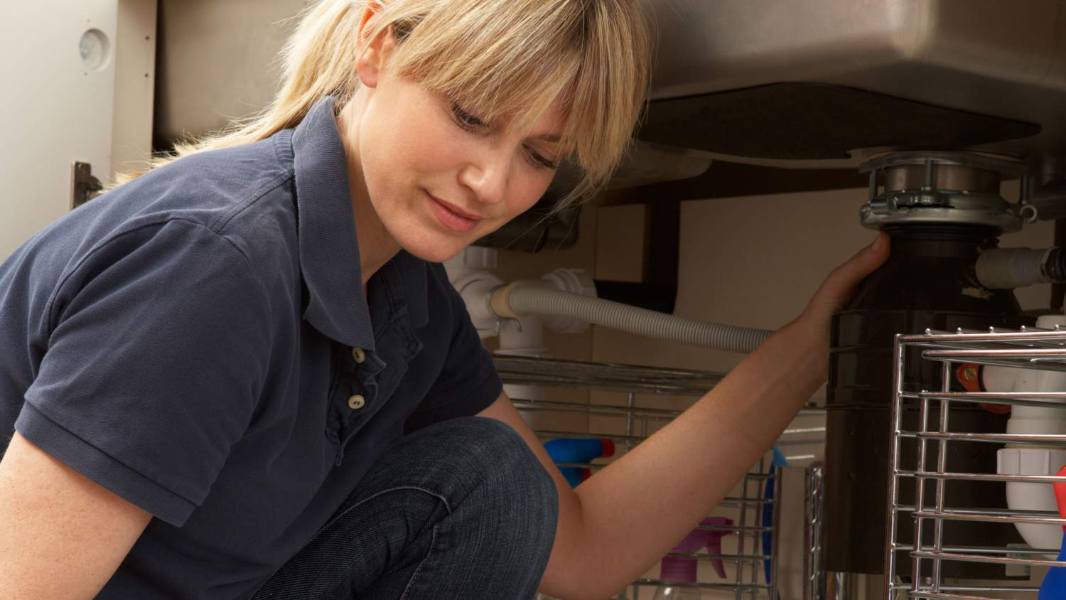 Female plumber fixing a leak