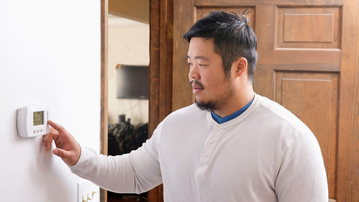 Tran family dad changing the thermostat
