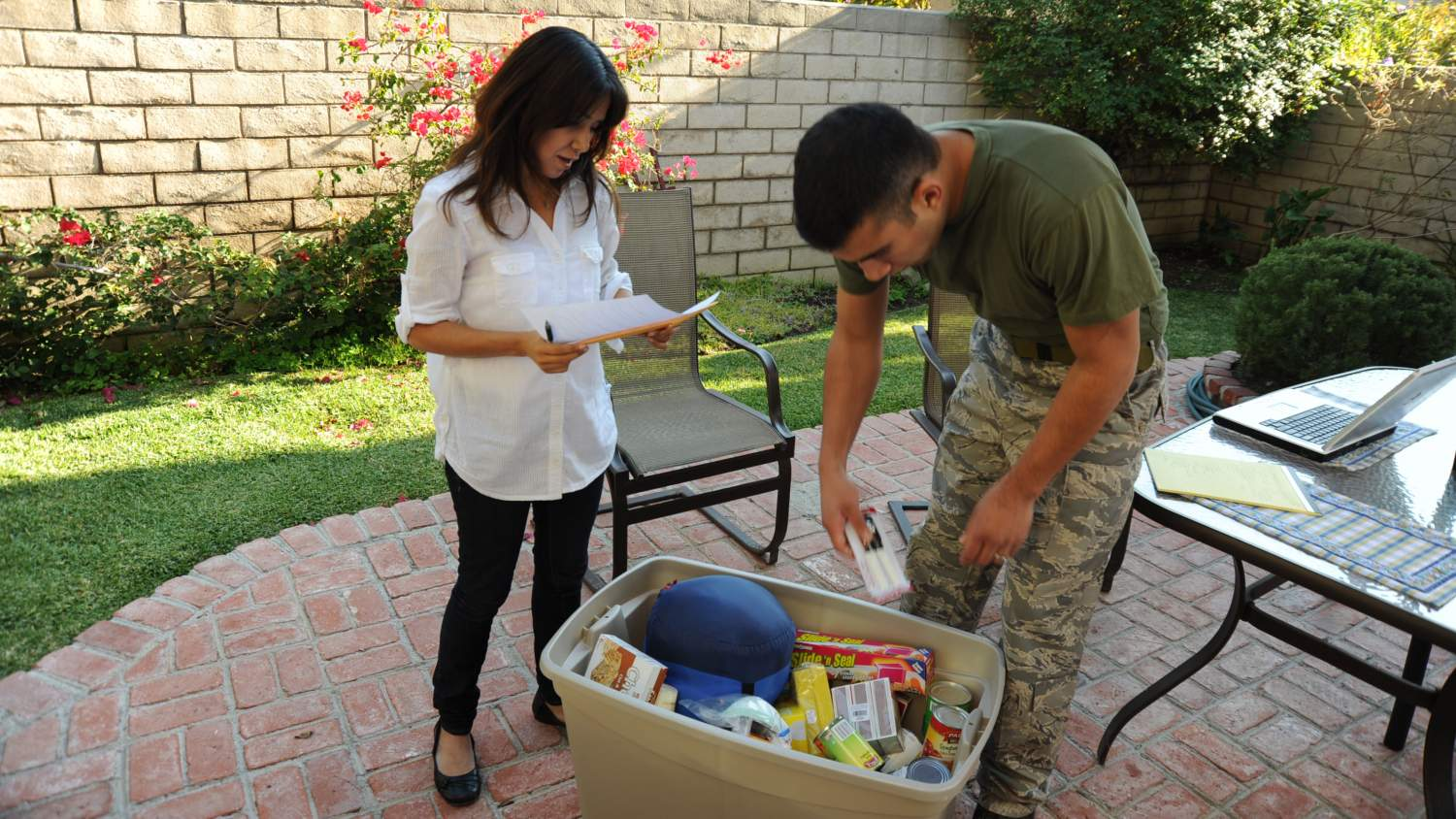 Military couple putting together a disaster preparedness kit