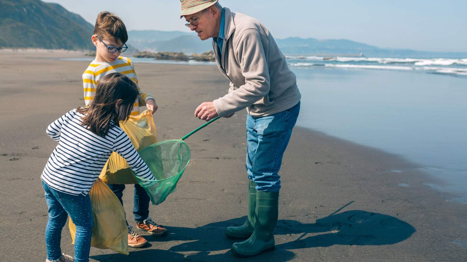 Kids and their grandfather at a beach clean-up