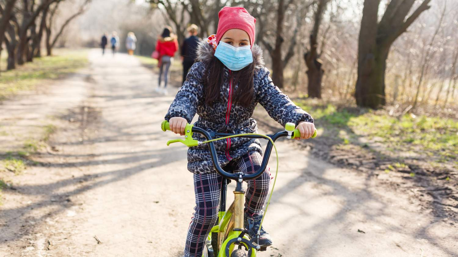 Girl with a mask on riding a bike