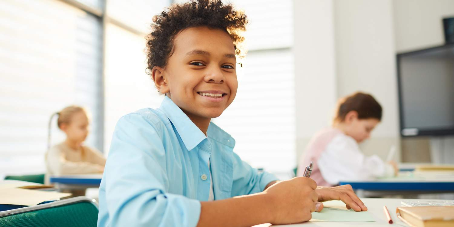 Smiling middle school student at a desk in class
