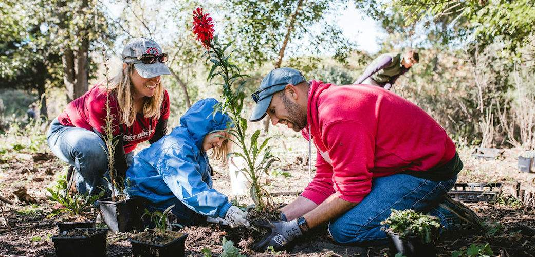 family planting a tree for National Public Lands Day event