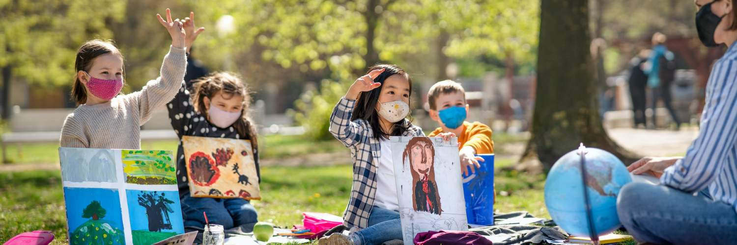 young students wearing masks in a park for an outdoor school lesson
