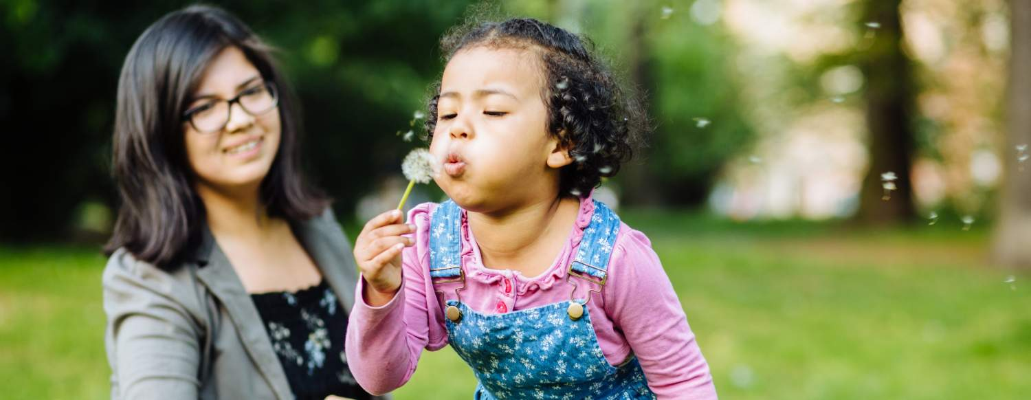 child blowing on a flower in the park with her mother