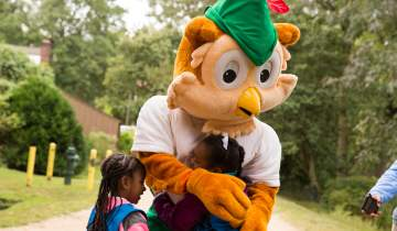 Woodsy Owl hugging a Girl Scout