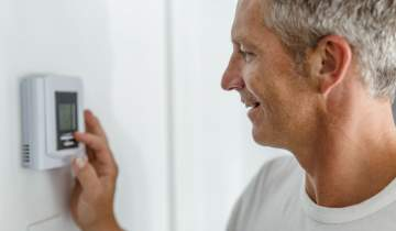 Smiling daddy adjusting the thermostat