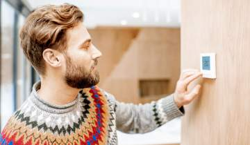 Man in sweater adjusting thermostat