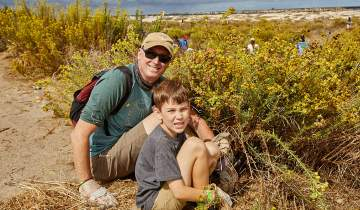 Dad and son planting at San Diego River Mouth