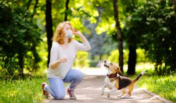 Woman in a face mask at the park with her dog