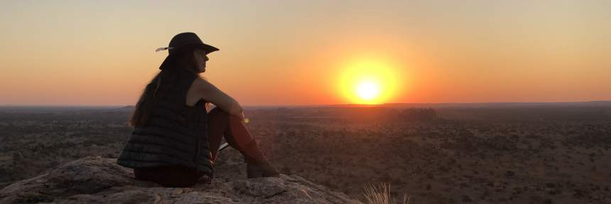 Woman looking out over sunset in Botswana