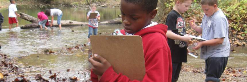 Children learning and observing at a creek bed