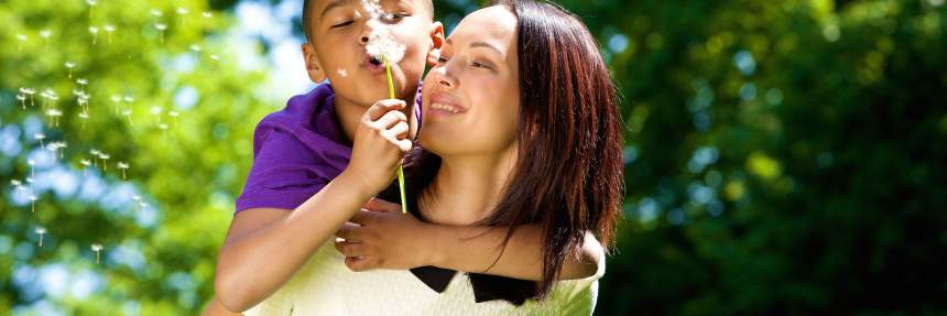 Boy blowing a dandelion with his mom