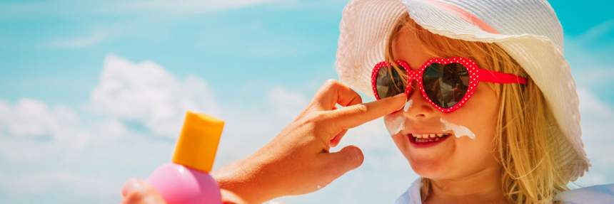 Girl getting sunscreen put on her nose