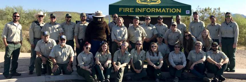 US Forest service officials group picture with Smokey the Bear