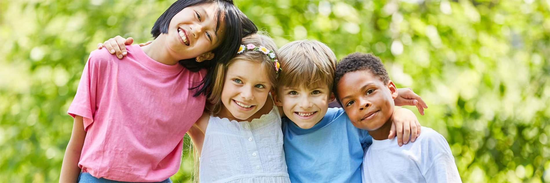 Four children smiling outdoors