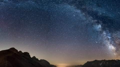 The Milky Way arch starry sky over mountains