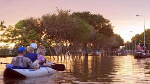 People in a canoe on a flooded city street