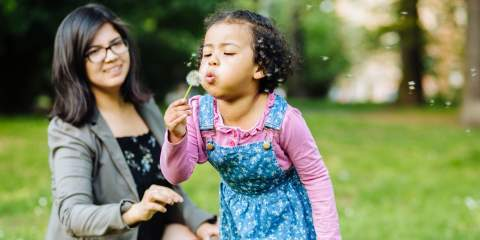 Daughter blowing on a dandelion while her mom watches